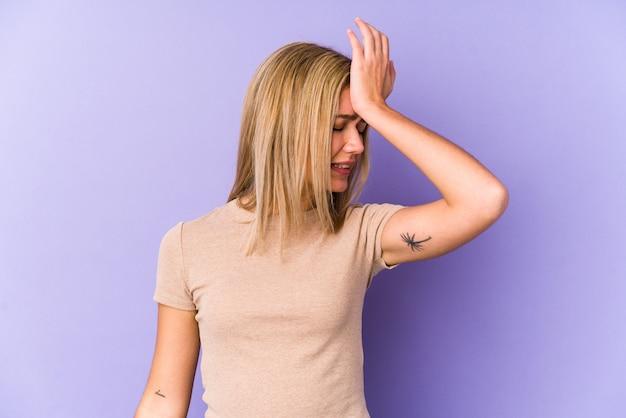 Jovem mulher caucasiana loira isolada esquecendo algo, batendo na testa com a palma da mão e fechando os olhos.