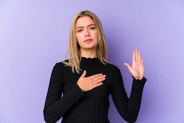 Jovem mulher caucasiana loira isolada fazendo um juramento, colocando a mão no peito.