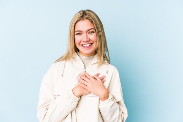 Jovem mulher caucasiana loira isolada tem expressão amigável, pressionando a palma da mão no peito. conceito de amor