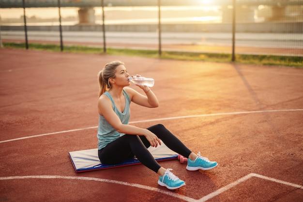 Jovem mulher caucasiana loira no sportswear, sentado no tapete na quadra e água potável após o exercício.