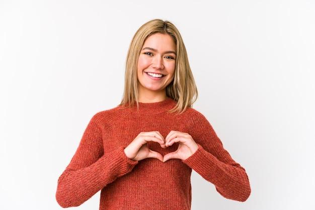 Jovem mulher caucasiana loira sorrindo e mostrando uma forma de coração com as mãos.