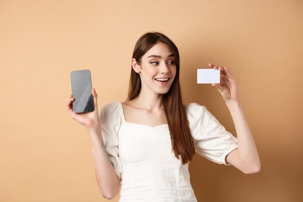 Jovem mulher caucasiana, mostrando o cartão de crédito de plástico com um sorriso satisfeito, demonstra a tela do celular vazia, de pé sobre um fundo bege.