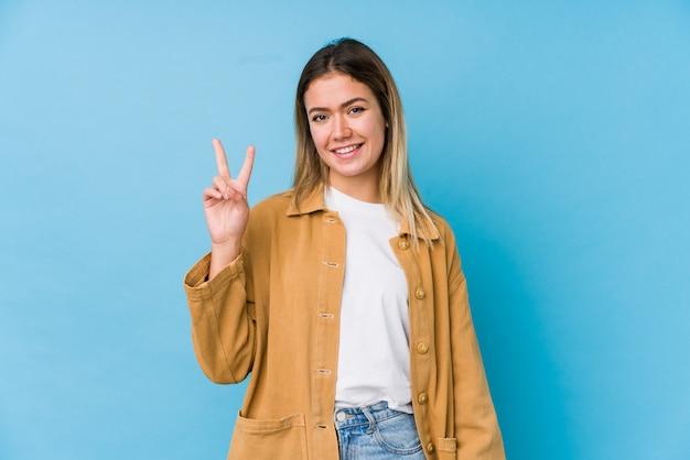 Jovem mulher caucasiana, mostrando o número dois com os dedos.