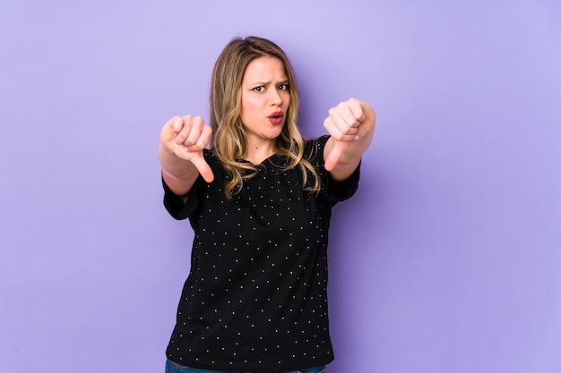 Jovem mulher caucasiana, mostrando o polegar para baixo e expressando antipatia.