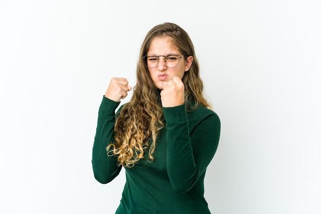 Jovem mulher caucasiana, mostrando o punho para a câmera, expressão facial agressiva.