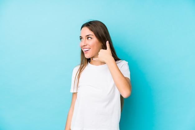 Jovem mulher caucasiana, mostrando um gesto de chamada de celular com os dedos.