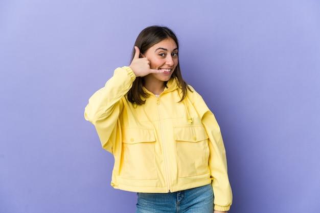 Jovem mulher caucasiana, mostrando um gesto de chamada de telefone móvel com os dedos.