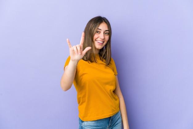 Jovem mulher caucasiana, mostrando um gesto de chifres como um conceito de revolução.