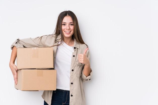 Jovem mulher caucasiana, movendo-se para uma nova casa, sorrindo e levantando o polegar