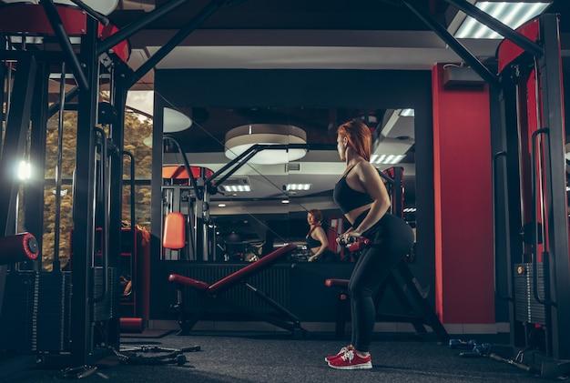 Jovem mulher caucasiana muscular praticando na academia com equipamento. bem-estar, estilo de vida saudável, musculação.