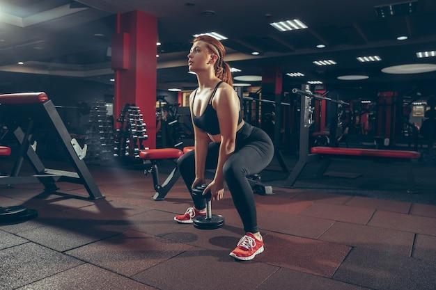 Jovem mulher caucasiana musculosa praticando academia com equipamentos de bem-estar estilo de vida saudável