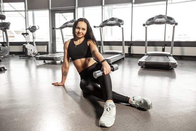 Jovem mulher caucasiana musculosa praticando academia com equipamentos