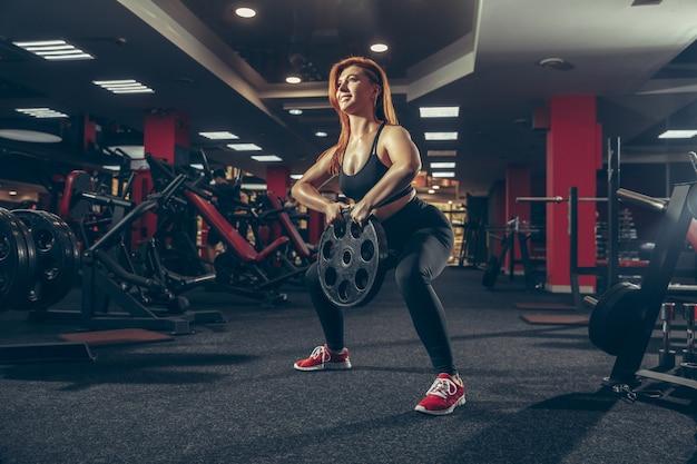 Jovem mulher caucasiana musculosa praticando na academia com equipamentos de bem-estar estilo de vida saudável
