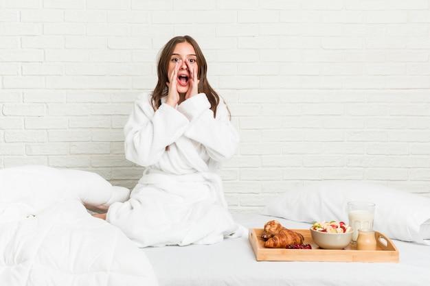 Jovem mulher caucasiana na cama gritando animado para a frente.