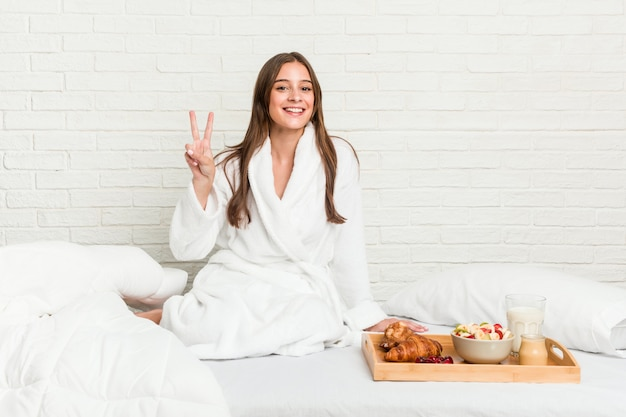 Jovem mulher caucasiana na cama mostrando sinal de vitória e sorrindo amplamente.