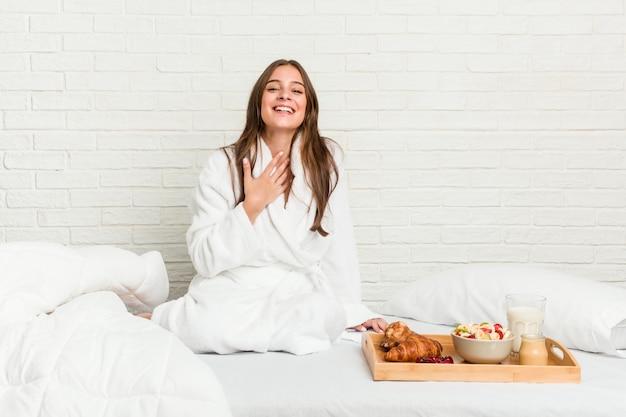 Jovem mulher caucasiana na cama ri alto, mantendo a mão no peito.