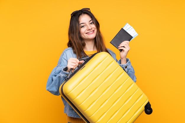 Jovem mulher caucasiana na parede amarela em férias com mala e passaporte