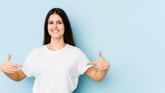 Jovem mulher caucasiana na parede azul aponta para baixo com os dedos, sentimento positivo.