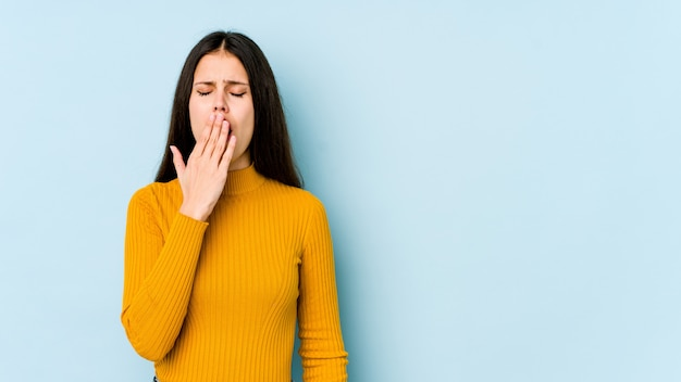 Jovem mulher caucasiana na parede azul bocejando mostrando um gesto cansado, cobrindo a boca com a mão.