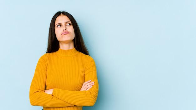 Jovem mulher caucasiana na parede azul cansada de uma tarefa repetitiva.