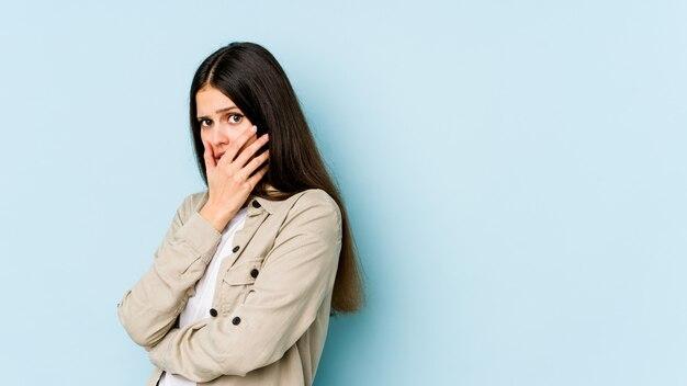 Jovem mulher caucasiana na parede azul com medo e medo.