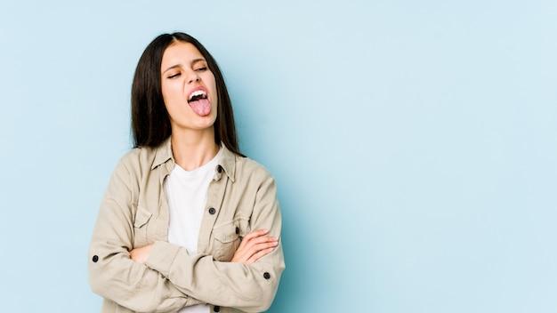 Jovem mulher caucasiana na parede azul engraçada e amigável saindo da língua.