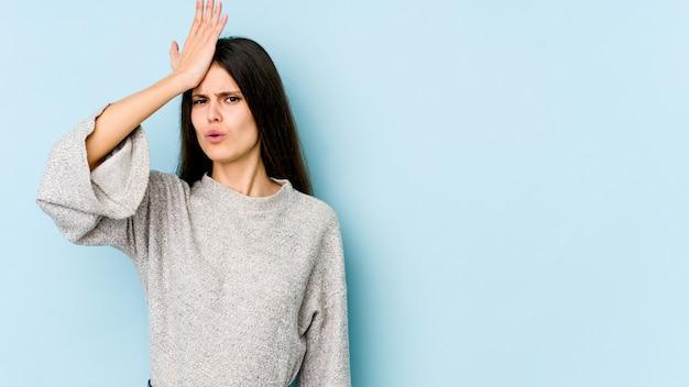 Jovem mulher caucasiana na parede azul, esquecendo algo, batendo na testa com a palma da mão e fechando os olhos.