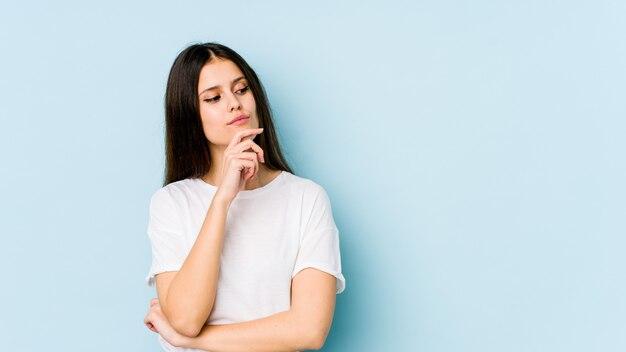 Jovem mulher caucasiana na parede azul, olhando de soslaio com expressão duvidosa e cética.