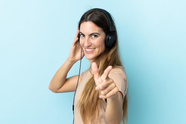 Jovem mulher caucasiana na parede azul, ouvindo música e apontando para a frente