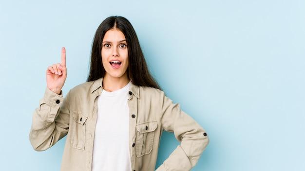 Jovem mulher caucasiana na parede azul, tendo uma ideia