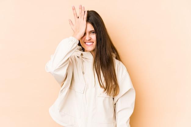 Jovem mulher caucasiana na parede bege, esquecendo algo, batendo na testa com a palma da mão e fechando os olhos.