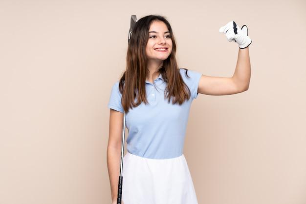 Jovem mulher caucasiana na parede bege jogando golfe e comemorando uma vitória
