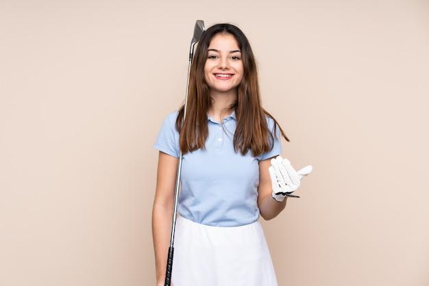 Jovem mulher caucasiana na parede bege jogando golfe e fazendo gesto próximo