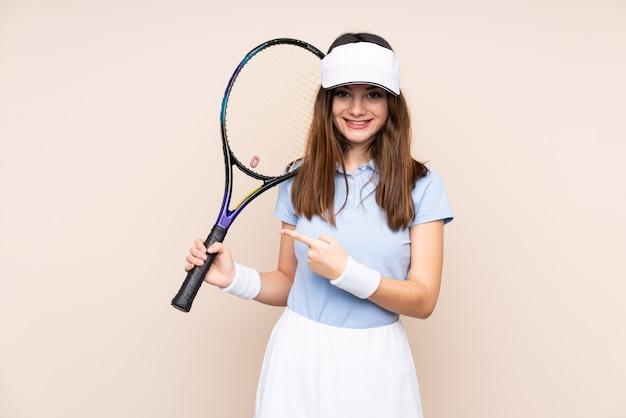 Jovem mulher caucasiana na parede bege jogando tênis e apontando para a lateral