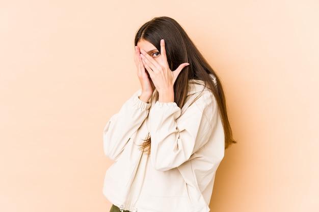 Jovem mulher caucasiana na parede bege pisca entre os dedos, assustada e nervosa.