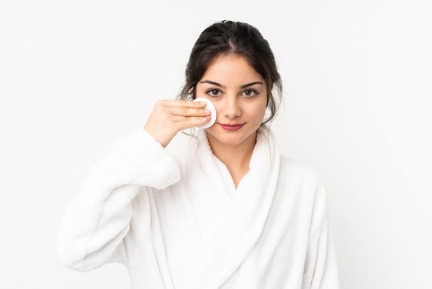 Jovem mulher caucasiana na parede branca com almofada de algodão para remover a maquiagem do rosto