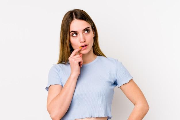Jovem mulher caucasiana na parede branca, olhando de soslaio com expressão duvidosa e cética.