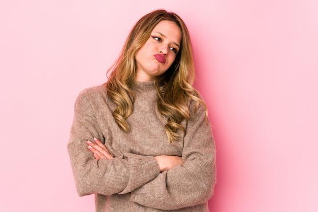 Jovem mulher caucasiana na parede rosa cansado de uma tarefa repetitiva.