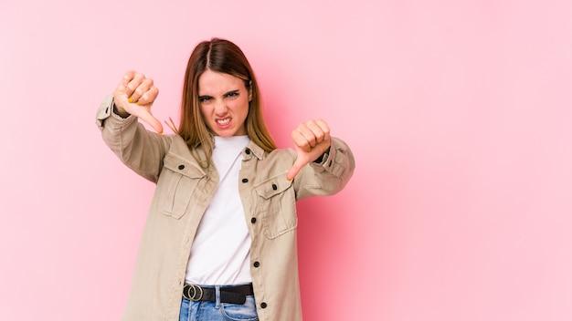 Jovem mulher caucasiana na parede rosa, mostrando o polegar para baixo e expressando antipatia.