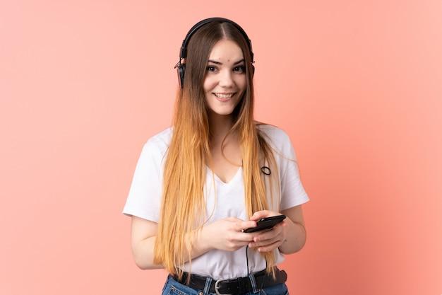 Jovem mulher caucasiana na parede rosa, ouvindo música com um celular e olhando de frente