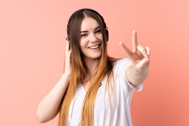 Jovem mulher caucasiana na parede rosa, ouvir música e cantar