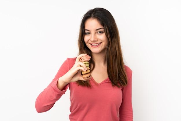 Jovem mulher caucasiana na parede rosa segurando macarons franceses coloridos e com expressão feliz