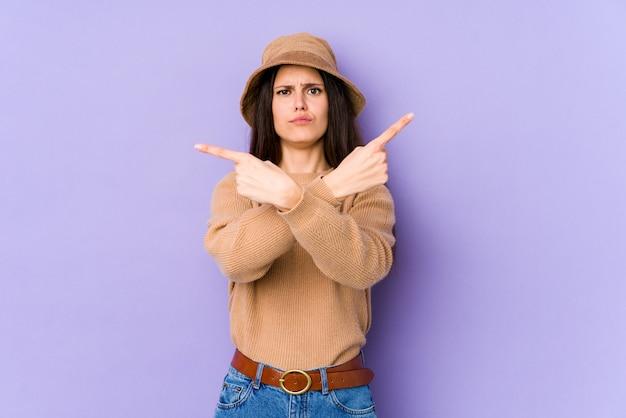 Jovem mulher caucasiana na parede roxa aponta lateralmente, está tentando escolher entre duas opções.