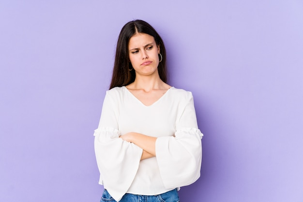 Jovem mulher caucasiana na parede roxa cansada de uma tarefa repetitiva.