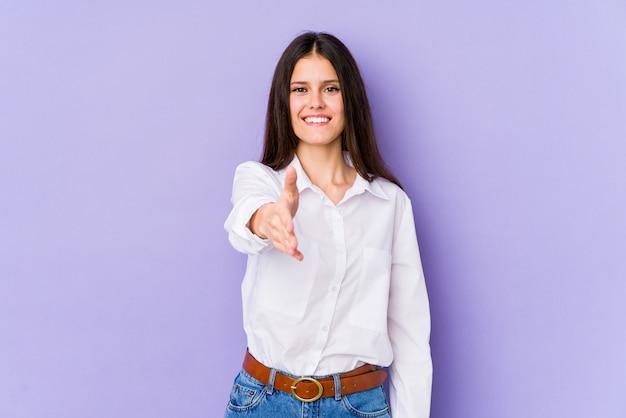 Jovem mulher caucasiana na parede roxa, esticando a mão na câmera em gesto de saudação.