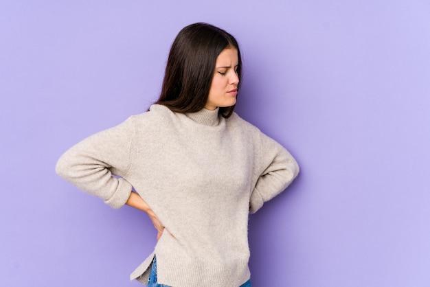 Jovem mulher caucasiana na parede roxa, sofrendo uma dor nas costas.