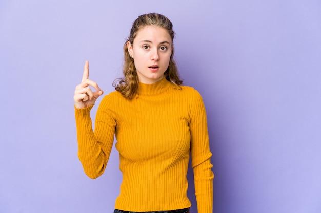 Jovem mulher caucasiana na parede roxa, tendo uma ideia