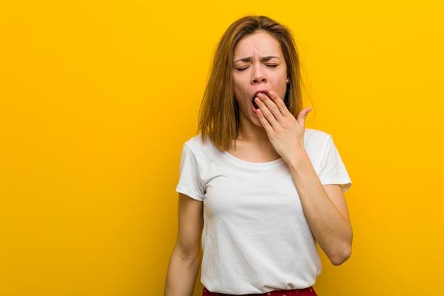 Jovem mulher caucasiana natural bocejando, mostrando um gesto cansado, cobrindo a boca com a mão.
