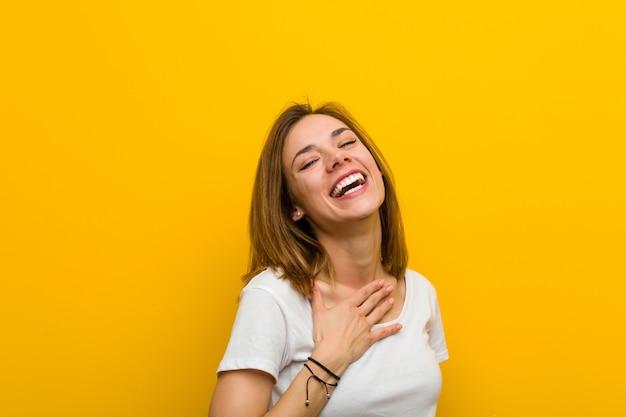 Jovem mulher caucasiana natural ri em voz alta, mantendo a mão no peito.