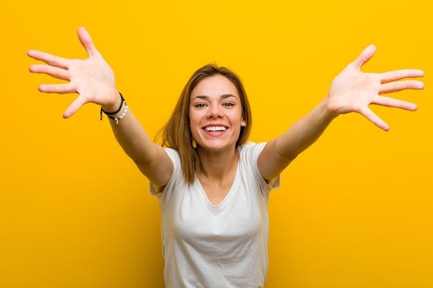 Jovem mulher caucasiana natural se sente confiante para dar um abraço